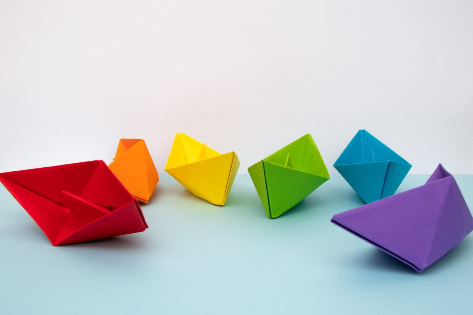 Coloured paper boats with the colours of the rainbow